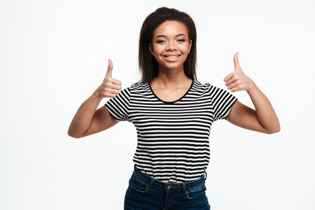 Portrait of a happy smiling afro american woman showing two thumbs up isolated over white background