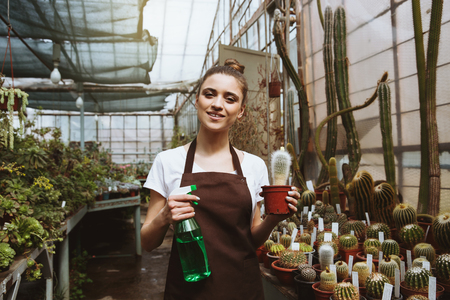 Image of happy young woman standing in greenhouse near plants. Looking at camera. 版權商用圖片