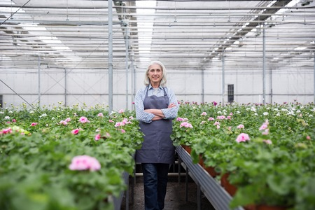 Image of happy mature woman standing in greenhouse near plants. Looking at camera.