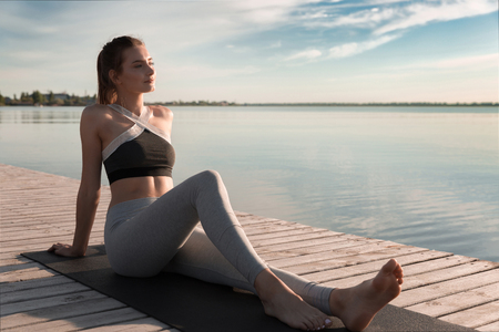 Image of young sports beautiful woman at the beach sitting looking aside.