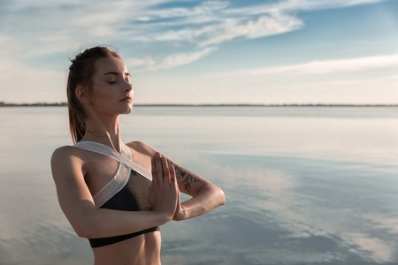 Picture of young sports beautiful woman at the beach make meditation exercises. 版權商用圖片