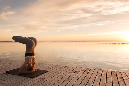 Picture of attractive young sports lady at the beach make yoga exercises.