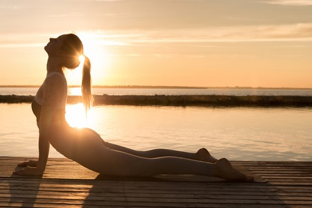 Image of amazing young sports lady at the beach make yoga exercises.
