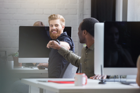 Smiling bearded man giving a fist bump to a male colleague while they are sitting at their computer desks 스톡 콘텐츠