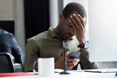 Upset young african man reading message on his mobile phone while sitting at his desk