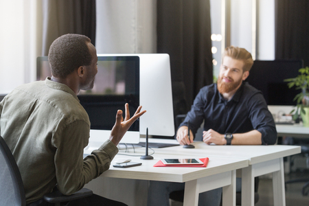 Two young male colleagues sitting at opposing desks and discussing new startup project at the office Stock Photo