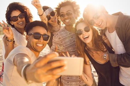 Gruppo di amici felici multirazziale che prendono selfie e divertirsi su una spiaggia Archivio Fotografico - 81802987