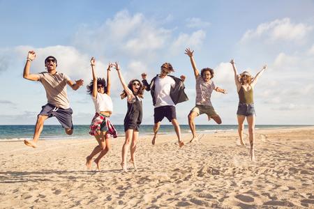 해변에서 점프하는 흥분된 젊은 친구의 초상화 스톡 콘텐츠