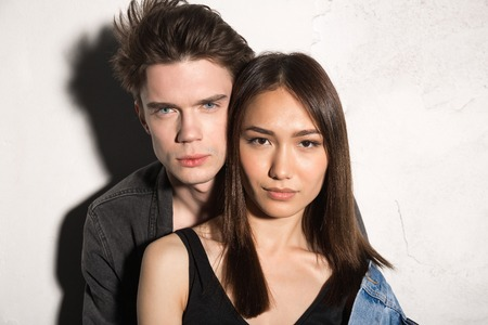 rudeness: Picture of serious young hipster loving couple looking at camera over gray background