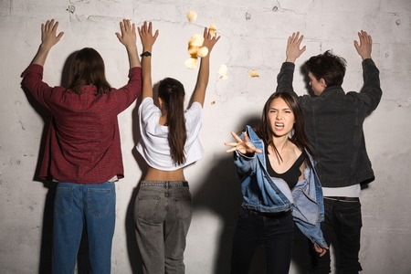 Image of young angry hipsters loving couples standing over gray background. Woman scatter bread Looking camera. Stock Photo