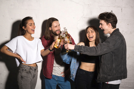 supercilious: Image of young hipsters friends standing over gray background drinking beer. Stock Photo