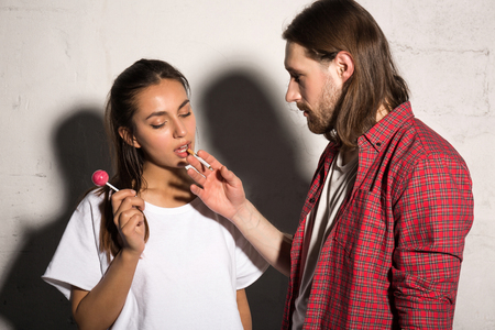 supercilious: Young hipster man standing over gray background give cigarette to girlfriend holding candy.