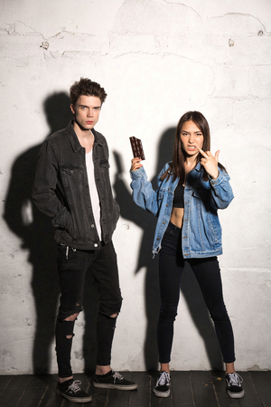 Image of young hipster woman standing over gray background near boyfriend holding chocolate showing middle finger. Stock Photo
