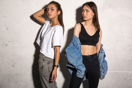 supercilious: Picture of concentrated young hipsters ladies standing over gray background.