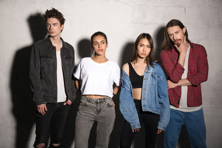 supercilious: Image of concentrated young hipsters friends standing over gray background. Looking aside. Stock Photo