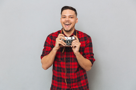 Happy Man in shirt making photo on retro camera over gray background