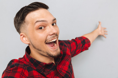 Happy man in red shirt standing sideways and posing in studio over gray background. Close up picture