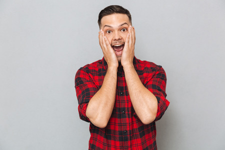 funny bearded man: Surprised happy manin shirt  holding his cheeks with open mouth and looking at the camera over gray background Stock Photo
