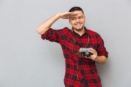 Man in red shirt holding his retro camera and looking at the  camera over gray background