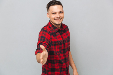 Smiling man in red shirt holds out his hand for a handshake and looking at the camera over gray background Stock Photo