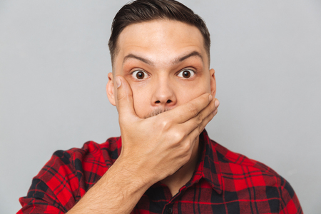 Close up portrait of a Shocked man in shirt covering his mouth and looking at the camera over gray background Stok Fotoğraf