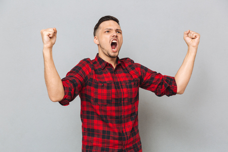 funny bearded man: Screaming man in shirt showing happy gestures and looking away over gray background Stock Photo