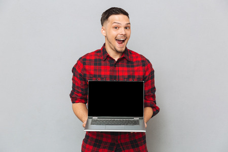 funny bearded man: Happy man in red shirt showing laptop computer screen at the camera over gray background Stock Photo