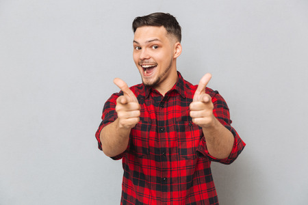 funny bearded man: Happy man in red shirt  showing thumbs up at the  camera over gray background
