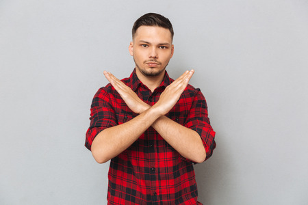Serious man in shirt showing stop gesture and looking at the camera over gray background