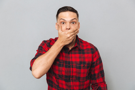 Shocked man in shirt covering his mouth and looking at the camera over gray background Stok Fotoğraf