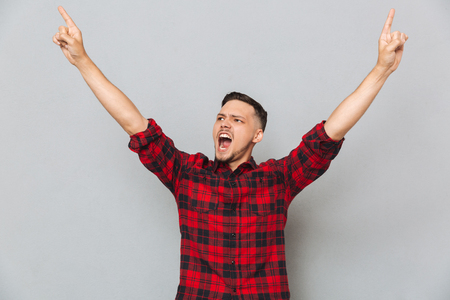funny bearded man: Happy screaming man in shirt pointing up and looking away over gray background Stock Photo