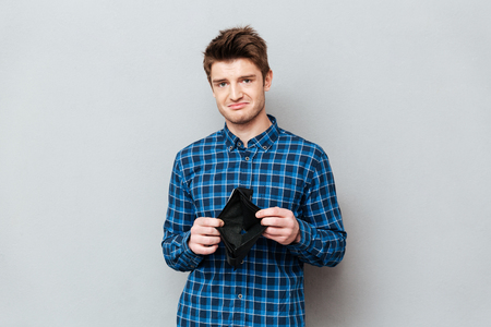 Picture of young sad man standing over grey wall and looking at camera while holding purse without money. Reklamní fotografie - 82044646