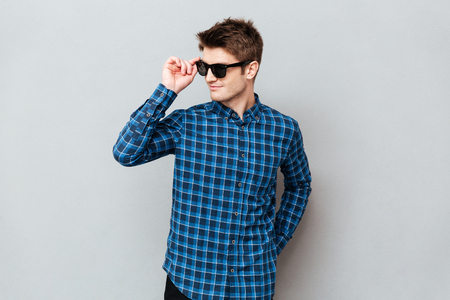Image of young cheerful man wearing sunglasses standing over grey wall and looking aside.