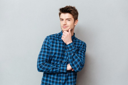 Thoughtful young man looking camera with folded hands isolated over grey