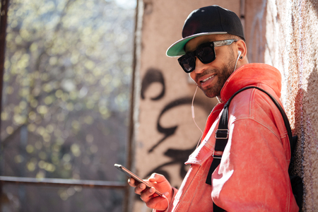 Portrait of a happy stylish afro american man in sunglasses listening music with mobile phone and earphones while leaning on a street wall