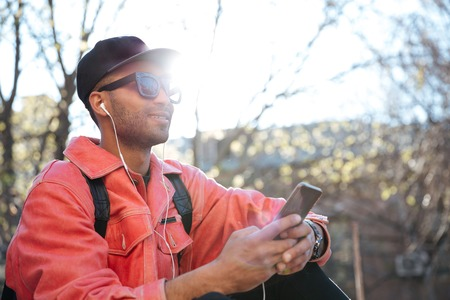 Image of handsome smiling young african man sitting outdoors in park wearing sunglasses and cap using mobile phone and listening music with earphones. Looking aside.