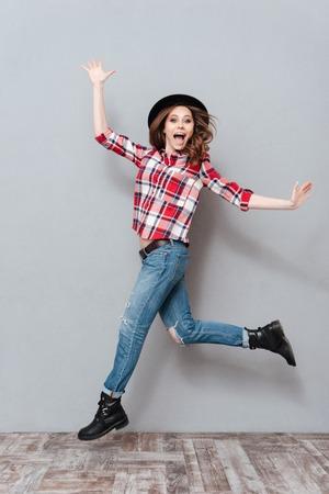 灰色の背景の上分離された成功を祝う格子縞のシャツで屈託のない幸せな女の子の完全な長さの肖像画 写真素材
