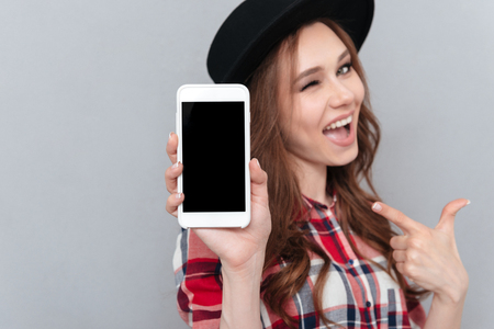 Close up portrait of a casual pretty woman in hat winking and pointing finger at blank mobile phone screen isolated over gray background