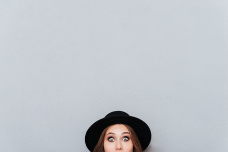 Portrait of a surprised young woman in hat peeping out from the edge and looking at camera isolated over gray background Banco de Imagens - 82148455