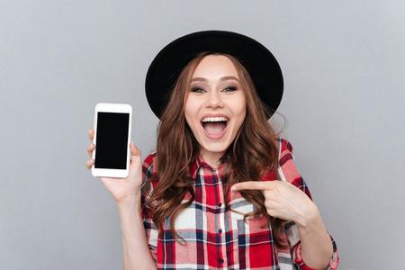 幸せのポートレート興奮灰色の背景上分離された空白の画面携帯電話でカジュアルな女性の人差し指 写真素材 - 82148456