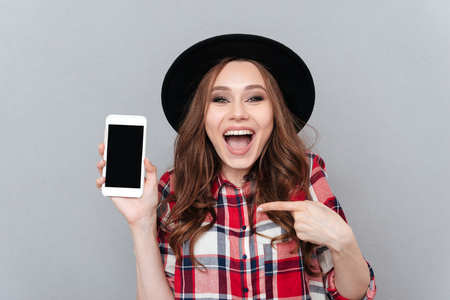 Portrait of a happy excited casual woman pointing finger at blank screen mobile phone isolated over gray background