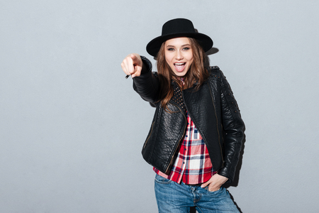 Portrait of an excited young woman in hat and leather jacket pointing finger at camera isolated over gray background