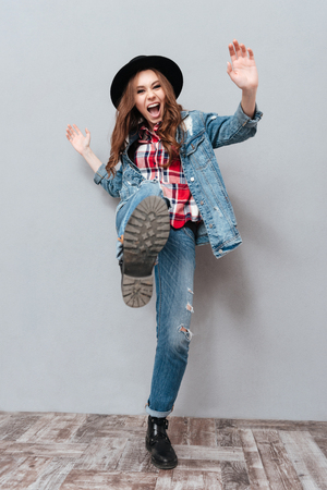 Full length portrait of a happy excited woman in hat celebrating win with foot raised isolated over gray background