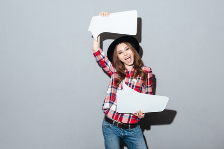 Image of happy young woman standing over grey wall wearing hat holding speech bubble. Looking at camera. Reklamní fotografie