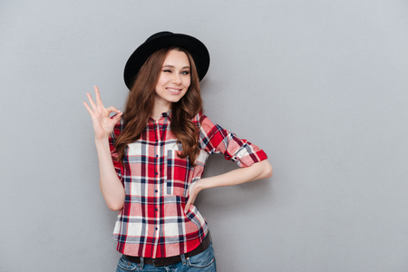 Portrait of a young positive girl in plaid shoort showing ok gesture and winking isolated over gray background Stock Photo