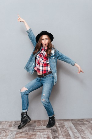 Full length portrait of an excited happy girl in hat celebrating success isolated over gray background Stock Photo