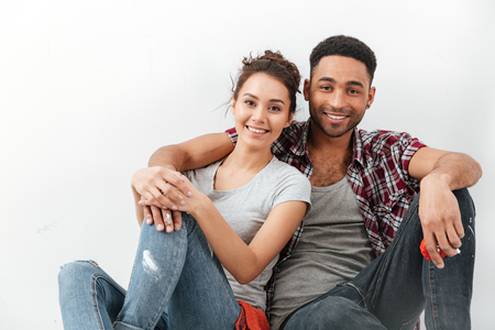 Smiling beautiful multiethnic young couple sitting and hugging over white background 版權商用圖片 - 82086025