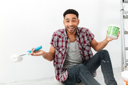 Portrait of sitting mulatte cheerful man on floor with repair equipment and dye isolated Stock Photo