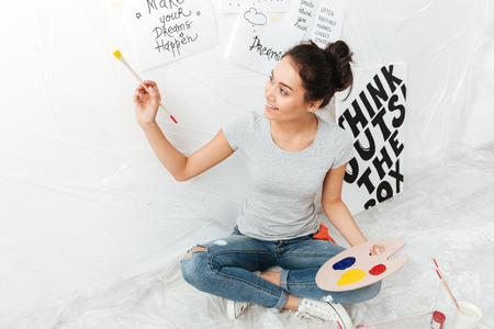 Image of happy young lady artist sitting on floor over white background. Looking aside.