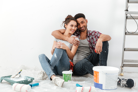 Happy multiethnic young couple renovating home and hugging over white background Stock Photo